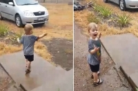 Little boy dances in the rain for the very first time as downpour soaks fire ravaged nsw